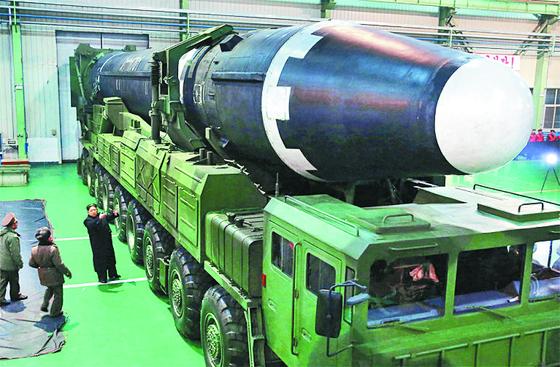 김정은 북한 노동당 위원장(왼쪽 아래)이 이동식발사대(TEL)에 실린 대륙간탄도미사일 (ICBM)급 화성-15형을 살펴보고 있다. [중앙포토]