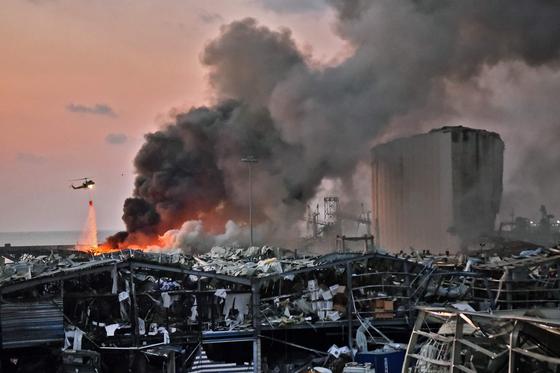 4일(현지 시간) 대규모 폭발사고가 발생한 레바논 베이루트 항구 현장에서 헬리콥터가 물을 뿌리며 진화작업을 진행하고 있다. AFP=연합뉴스