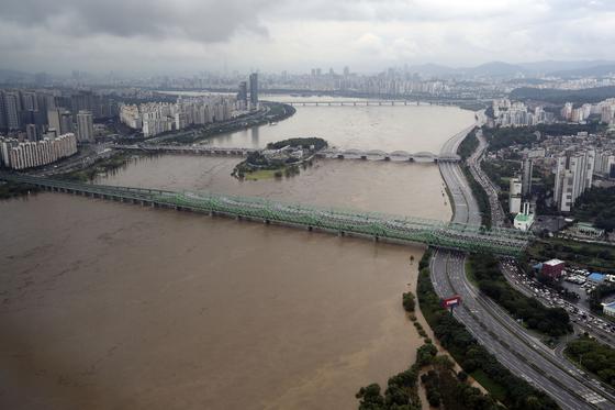 서울 전역에 호우특보가 발효된 지난 3일 오전 서울 영등포구 63아트에서 바라본 한강물이 불어 황토색으로 흐르고 있다. 한강 상류인 팔당댐이 방류량을 늘리면서 한강 수위가 오르자 오른쪽 올림픽대로가 통제되고 있다. 김성룡 기자