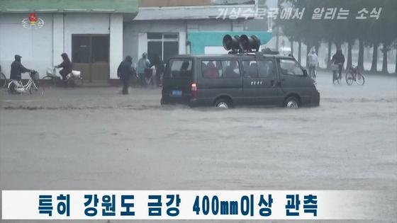 조선중앙TV가 5일 공개한 북한 강원도 지역의 폭우 상황. 도로에 흙탕물이 들어차고 자동차 바퀴가 절반 이상 잠겼다. [조선중앙TV 화면, 연합뉴스]
