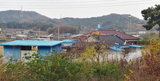 비료공장에서 나온 발암물질 때문에 암이 집단으로 발병한 전북 익산시 장점마을 인근의 장고재마을. 마을 뒤로 보이는 산 아래 하늘색 건물이 발암물질을 배출한 비료공장이다. [연합뉴스]
