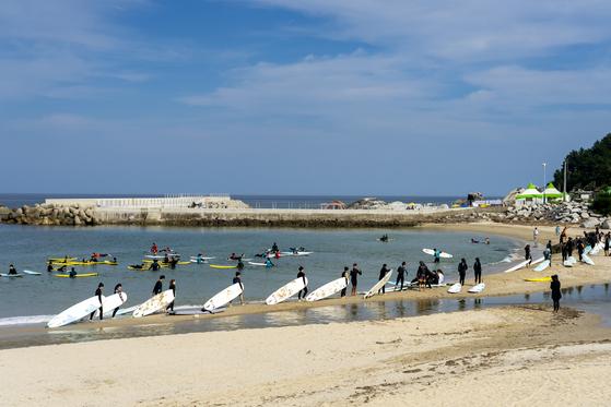 서핑 성지로 통하는 양양 인구 해변. 보드를 든 서퍼들이 해변을 따라 이동하고 있다. 백종현 기자