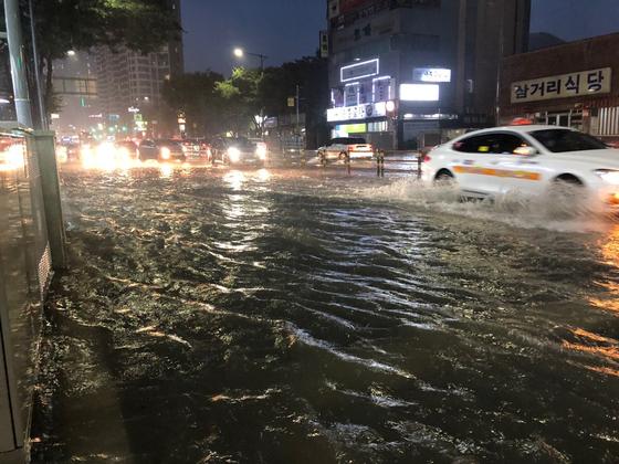 7일 오후 부산 해운대구 우동 한 도로에 물이 차올라 차량이 서행하고 있다. 부산 경찰청 제공=연합뉴스