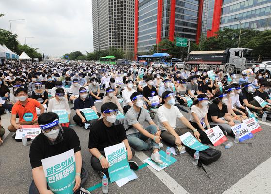 집단휴진에 들어간 의과대학 정원 확대 방안에 반대하는 전공의들이 7일 서울 영등포구 여의대로에서 피켓을 들고 있다. 뉴스1