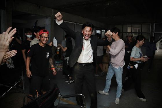 영화 '다만 악에서 구하소서' 주연 배우 황정민이 촬영 현장에서 환호를 질렀다. 그 왼쪽에서 빨간 모자를 쓰고 웃는 이가 '기생충'에 이어 이번 영화에 참여한 홍경표 촬영감독이다.  [사진 CJ엔터테인먼트]