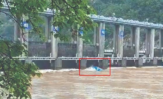 6일 오전 강원도 춘천시 의암댐 상부 500m 지점에서 뒤집힌 선박이 급류를 타고 수문으로 향하고 있다. [연합뉴스]
