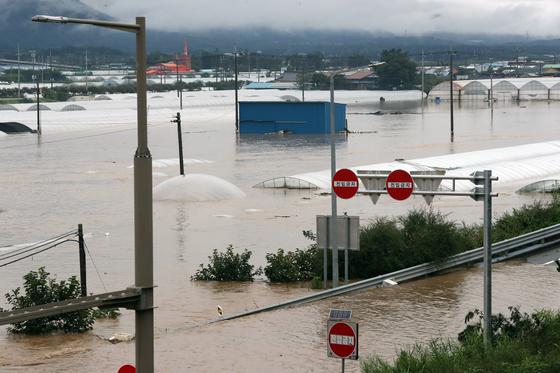 8일 오후 폭우로 전북 남원시 금지면 금곡교 인근 섬진강 제방 일부가 무너져 인근 비닐하우스와 주택이 물에 잠겨 있다. 연합뉴스,