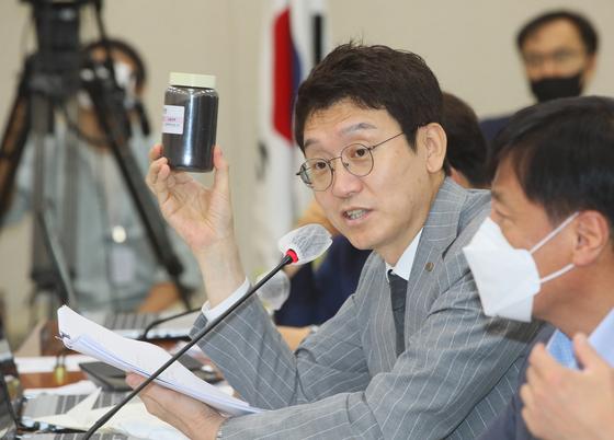 미래통합당 김웅 의원이 31일 국회 환경노동위원회 전체회의에서 '입상활성탄'을 보여주며 수돗물 유충 사태와 관련해 질의하고 있다.  연합뉴스