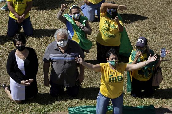브라질 대통령의 지지자들이 지난달 대통령의 건강을 기원하는 집회를 열고 있다. 참가자 중의 상당수가 노란색 셔츠를 입고 있다. [AP=연합뉴스]
