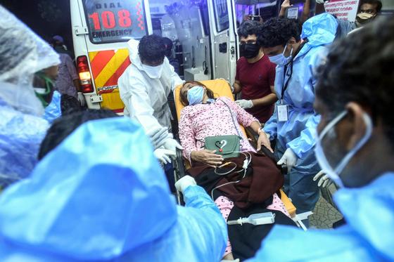 지난 7일 오후 인도 남부 케랄라주 코지코드 공항에서 폭우 속에 착륙하던 에어인디아 익스프레스 소속 여객기가 두동강 나는 사고가 났다. 사진은 구급대원들이 사고기에서 구조한 부상자를 이송하는 모습.[AFP=연합뉴스]