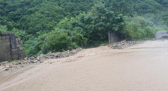 최고 200㎜가 넘는 폭우가 내린 3일 오전 강원 철원군 육단리의 침수 도로와 인접한 군부대 담장이 무너져 있다. [연합뉴스]