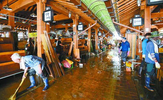 지난 9일 오후 경남 하동군 화개장터에서 상인들과 주민들이 섬진강 범람으로 침수된 상가를 복구하고 있다. [뉴시스]