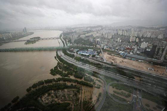 집중호우가 쏟아지며 한강 수위가 높아진 9일 오후 서울 영등포구 63스퀘어에서 바라본 통제된 올림픽대로와 흙탕물로 변한 한강. [연합뉴스]