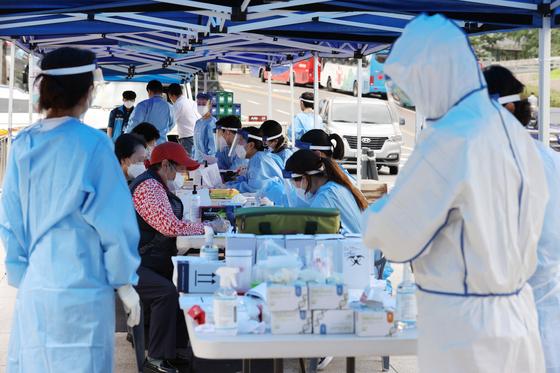 서울 중구 남대문시장의 한 상가에서 신종 코로나바이러스 감염증(코로나19) 확진자가 발생한 가운데 10일 오전 시장에 마련된 임시선별진료소에서 시민들이 진료를 받고 있다. 연합뉴스
