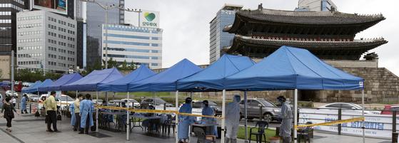 서울 중구 남대문시장의 한 상가에서 신종 코로나바이러스 감염증(코로나19) 확진자가 발생한 가운데 10일 오전 시장에 마련된 임시선별진료소에서 시민들이 코로나 검사를 받고 있다. 김성룡 기자