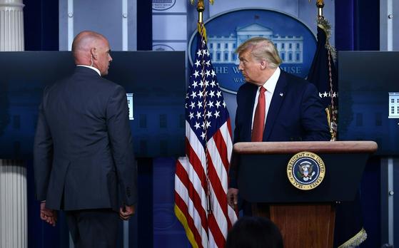 미 백악관 브리핑룸을 황급히 떠나는 트럼프 대통령. AP=연합뉴스
