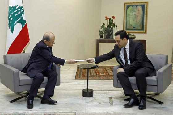 내각 총사퇴를 발표한 하산 디아브 총리(오른쪽)가 10일 미셸 아운 대통령에게 사표를 제출하고 있다. [AFP=연합뉴스]