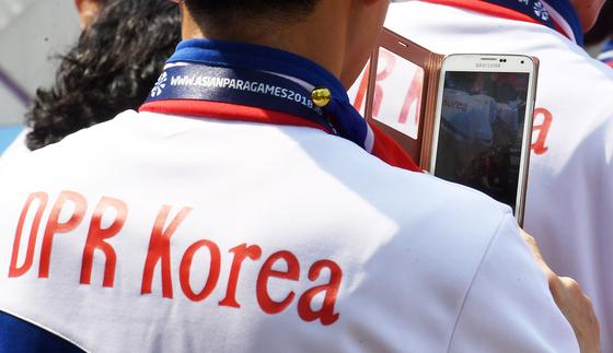 2018년 인도네시아 자카르타에서 열린 '2018 인도네시아 장애인아시아경기대회' 선수촌 입촌식에서 한 북한 선수가 스마트폰으로 행사 영상을 촬영하고 있다. 사진공동취재단