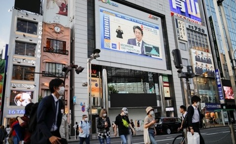 아베 신조 일본 총리의 신종 코로나바이러스 감염증(코로나19) 대응 관련 기자회견 모습이 지난 14일 도쿄 신주쿠의 한 건물에 설치된 대형 스크린을 통해 생중계되고 있다. 로이터=연합뉴스