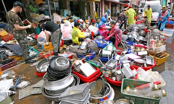 10일 오전 전남 구례군 구례읍 시장에서 현지 상인들이 집중호우로 침수된 식기류를 꺼내 세척하고 있다. [뉴스1]