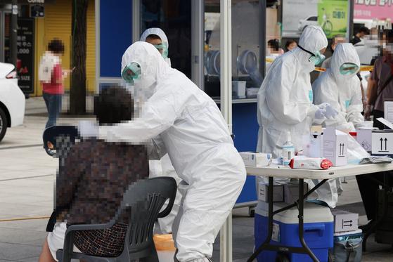최근 집단 신종 코로나바이러스 감염증 확진자가 나온 서울 중구 남대문시장에 마련한 임시선별 진료소에서 의료진이 검사를 하고 있다. 연합뉴스