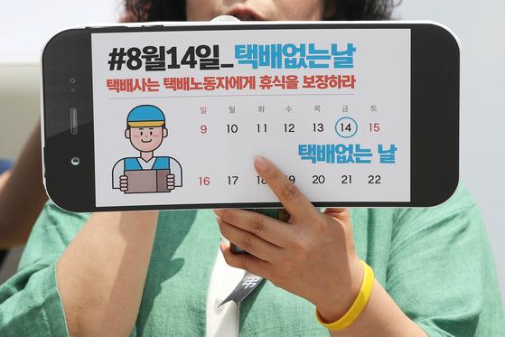 지난달 9일 오전 서울 광화문광장에서 열린 '8월 14일을 택배없는 날로 지정하라!' 기자회견에서 참석자가 택배 없는 날 지정을 촉구하는 손팻말을 들고 있다. 연합뉴스
