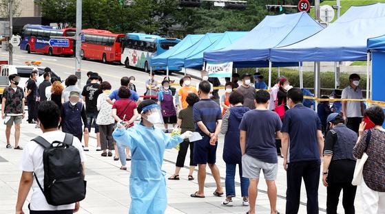 서울 남대문 시장에서 신종 코로나바이러스 감염증(코로나19) 확진자가 발생한 가운데 서울 중구 숭례문 앞에 설치된 선별진료소에서 시민들이 검사를 받고 있다. 뉴스1