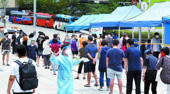 남대문 시장에서 신종 코로나바이러스 감염증(코로나19) 확진자가 발생한 가운데 서울 중구 숭례문 앞에 설치된 선별진료소에서 시민들이 검사를 받고 있다. 뉴스1