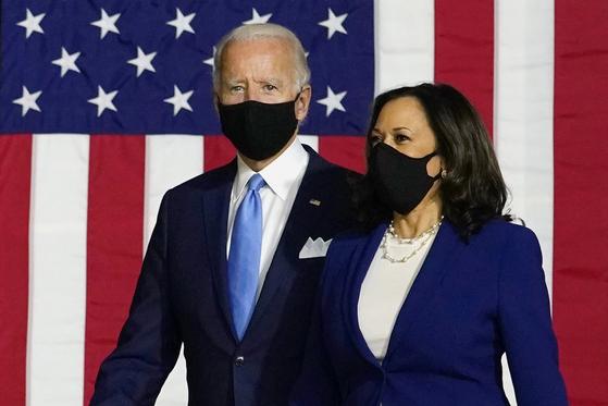미국 민주당 대통령 후보인 조 바이든(왼쪽)과 부통령 후보 카멀라 해리스가 12일(현지시간) 델라웨어주 윌밍턴의 한 고등학교 체육관에 마스크를 쓴 채 입장하고 있다. [AP=연합뉴스]