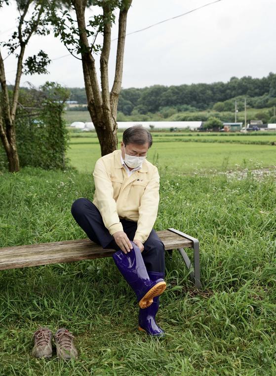 지난 12일 천안 수해지역을 찾은 문재인 대통령이 신발을 장화로 갈아신고 있다. [청와대사진기자단]