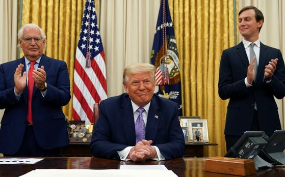 도널드 트럼프 미국 대통령이 13일(현지시간) 백악관 집무실에서 이스라엘과 아랍에미리트공화국(UAE) 간 외교관계 정상화 합의를 발표했다. 데비비드 프리드먼 이스라엘 주재 미국 대사(왼쪽)과 대통령 사위인 제러드 쿠슈너 백악관 선임고문이 박수치고 있다. [로이터=연합뉴스]