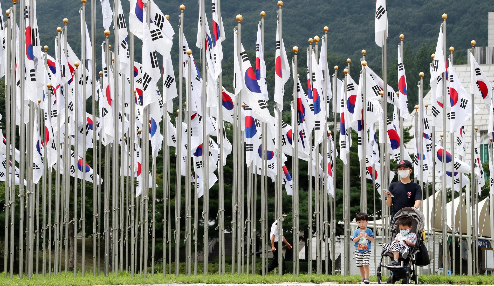 제75주년 광복절을 하루 앞둔 14일 오후 충남 천안 독립기념관을 찾은 관람객들이 태극기 마당에 게양된 태극기 사이로 걷고 있다. 뉴스1