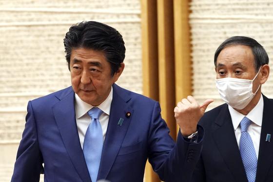 지난 5월 아베 신조 일본 총리와 스가 요시히데 관방장관이 코로나19 확산에 따른 긴급사태 선언 연장을 밝히고 있다. 최근 일본 정가에선 스가 장관이 '포스트 아베'로 유력하다는 관측이 나오고 있다. [AP=연합뉴스]