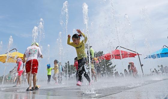 전국 대부분 지역에 폭염특보가 내려진 17일 울산시 동구 대왕암공원 내 바닥 분수대를 찾은 어린이들이 물놀이를 하며 더위를 식히고 있다. 18일과 19일까지도 전국에 타는듯한 더위가 이어질 것으로 보인다. 경북 경산은 19일 낮 최고 39도가 예상된다. 뉴스1