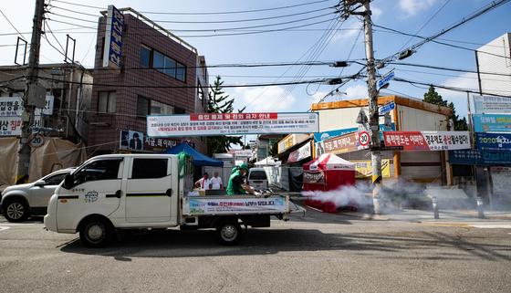 새마을지도자협의회 회원들이 17일 서울 성북구 사랑제일교회 인근에서 방역을 하고 있다. 뉴스1