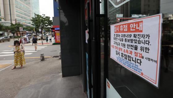 지난 12일 서울 광진구 롯데리아 군자점에 코로나19 확진자 관련 임시 휴점 안내문이 붙어 있다. 연합뉴스