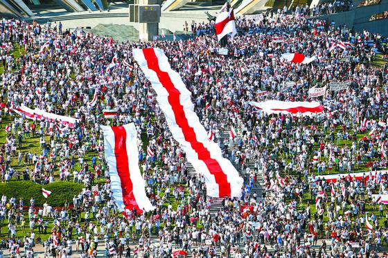 벨라루스 수도 민스크에서 16일 시위대가 대형 벨라루스 옛 깃발을 펼친 채 26년 동안 장기 집권해 온 알렉산드르 루카셴코 대통령의 퇴진을 요구하고 있다. [타스=연합뉴스]