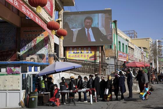 중국 신장위구르자치구 서쪽 허톈시 재래시장 입구의 보안검사대 뒤 대형 전광판에 시진핑 중국 국가주석의 동정 뉴스가 상영되고 있다. 지난 7월 미국 상무부는 11개 중국 기업을 신장에서의 인권 탄압에 연루됐다는 이유로 제재했다. [AP=연합뉴스]