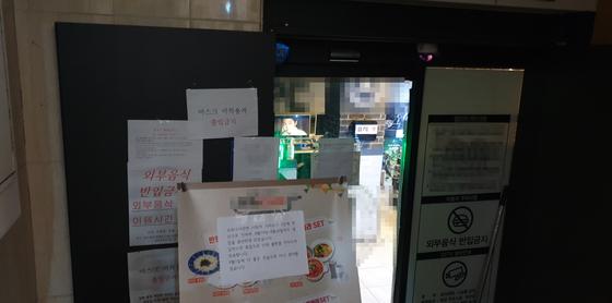 19일 오전 서울 서초구의 한 PC방. 영업을 중단한다는 안내문과 함께 입구는 막혀 있다. 업주가 문 닫은 PC방에서 영화를 보고 있다. 정진호 기자