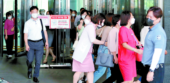 19일 서울시청 본관 2층 직원이 코로나19 확진 판정을 받아 청사가 폐쇄됐다. 이날 오후 직원들이 청사를 빠져나오고 있다. [뉴시스]