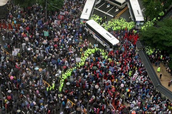 15일 서울 종로구 광화문 광장 열린 8ㆍ15 대규모 집회에 참가한 시민들이 집회를 마친후 경찰 저지선을 뚫고 사직로에서 청와대로 가던 중 경찰들과 대치하고 있다. 뉴시스.