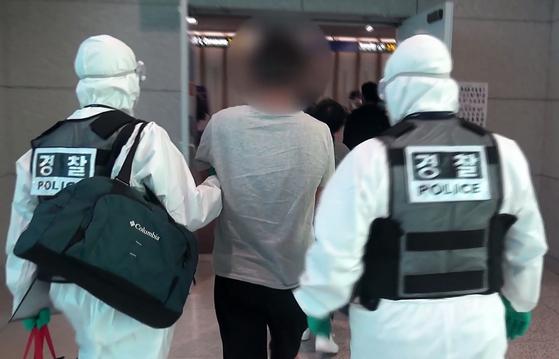 지난 4월 14일 태국에서 들어온 국제사이버범죄조직 총책을 체포하는 경찰. 코로나19 감염 가능성을 우려해 전신 방호복에 고글, 마스크를 착용했다. [사진 경기북부경찰청 제공]