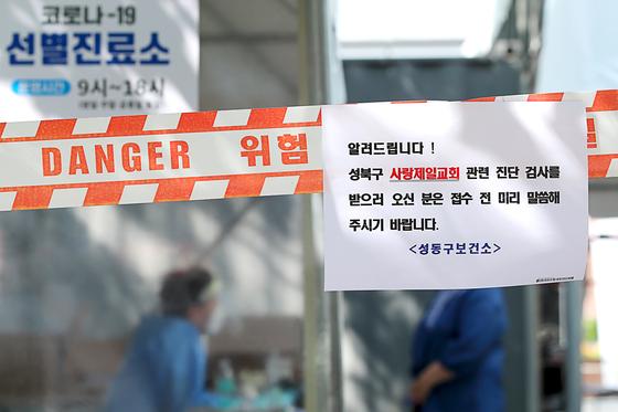 19일 오후 서울 성동구 선별진료소에 수도권 지역감염으로 인한 검사량이 많아짐에 따른 안내문이 붙어 있다. 뉴스1