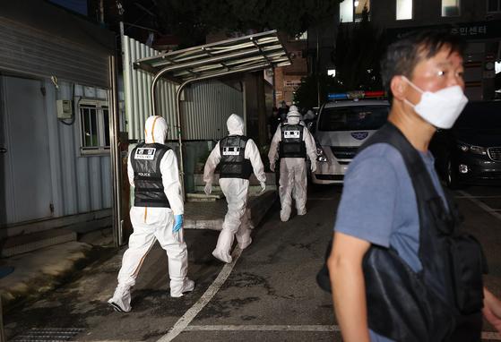 방호복을 입은 경찰이 21일 압수수색영장을 집행하기 위해 서울 성북구 사랑제일교회 입구로 이동하고 있다. [연합뉴스]