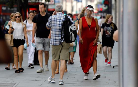 지난 12일 한 여성이 얼굴 가림막을 쓴 채 영국 런던 거리를 걷고 있다. [AFP=연합뉴스]