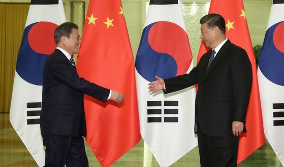 문재인 대통령 (왼쪽)은 지난해 12 월 정상 회담을 앞두고 베이징 인민 대표 대회에서 시진핑 중국 주석과 악수하고있다. [청와대사진기자단]