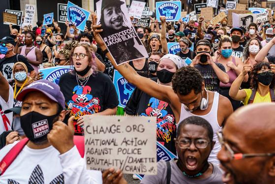 24일(현지시간) 미네소타주 미니애폴리스에서 제이콥 블레이크 총격 사건에 분노한 시위대가 경찰 개혁을 외치고 있다. 미니애폴리스는 지난 5월 경찰의 목 누르기 진압으로 흑인 조지 플로이드가 사망한 사건이 발생한 지역이다. [AFP=연합뉴스]
