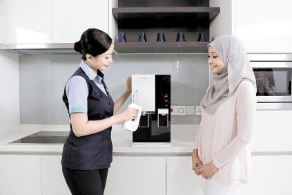 코웨이 말레이시아 법인의 현지 코디가 고객에게 정수기 사용법을 설명하고 있다. 2분기 말레이시아 법인의 관리계정 수는 전년 대비 32% 증가해 코웨이가 탄탄한 해외사업 실적을 올리는 데 큰 역할을 했다. [사진 코웨이]