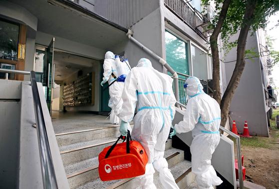 26일 오후 코로나19 집단감염이 발생한 서울 구로구 한 아파트에서 보건소 직원들이 방역을 하고 있다. 뉴시스.
