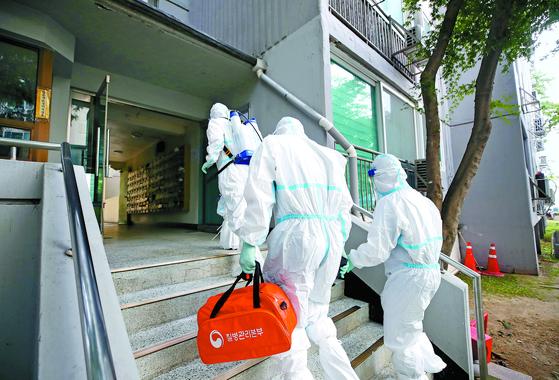 26일 코로나19 집단감염이 발생한 서울 구로구 아파트에서 보건소 직원들이 방역을 하고 있다. [뉴시스]